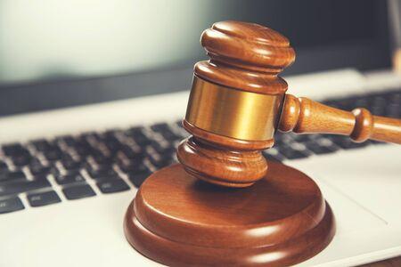 drewniany sędzia na klawiaturze komputera na drewnianym biurku