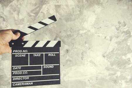 man hand  movie clapper on gray background