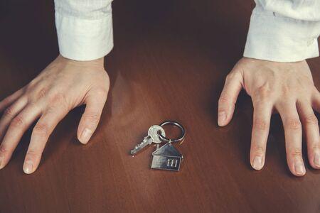 woman hand house key on the desk