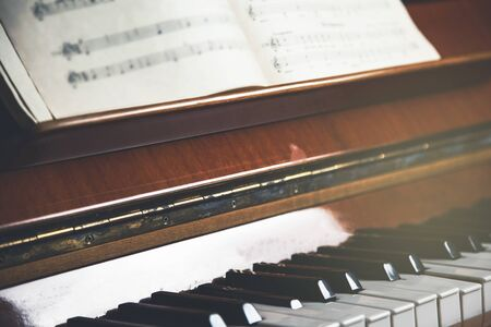 white music book on the brown piano