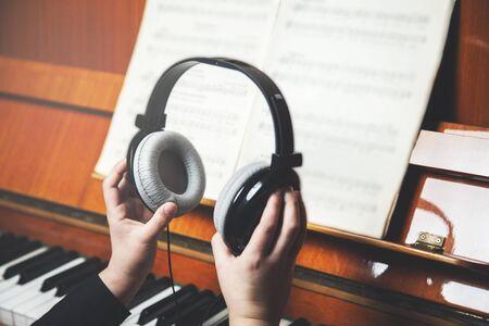 girl hand headphones and music book with piano Zdjęcie Seryjne