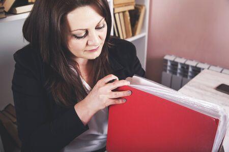 Businesswoman taking binders from a shelf at office Reklamní fotografie