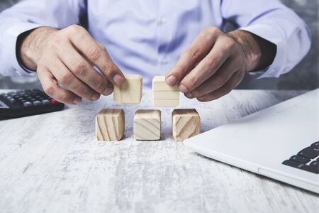 young business man hand wooden cubes on desk