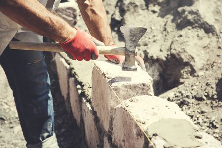 The man builder is building a wall
