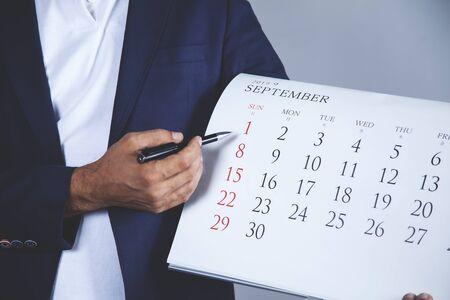 business man hand pen with calendar on gray background Reklamní fotografie