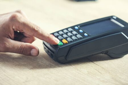 man hand payment terminal on the desk