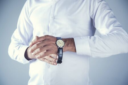 young business man hand  watch on gray background