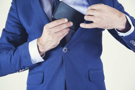 business man hand holding phone in pocket