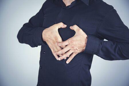 Mann Hand im Herzen auf dem grauen Wandhintergrund