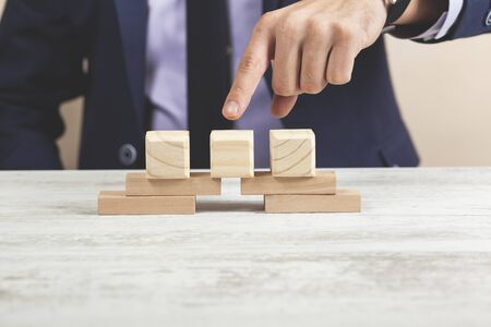 business man hand wooden cubes on the table