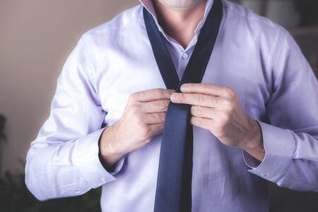young business man hand tie with shirt