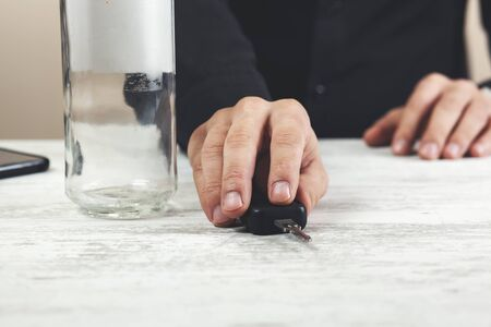 man hand bottle with car key on the table