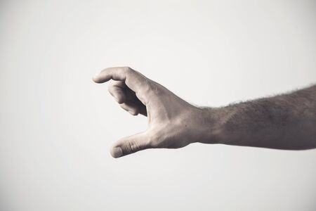 Fingers on the palm on a gray background. Hand sign. Little bit