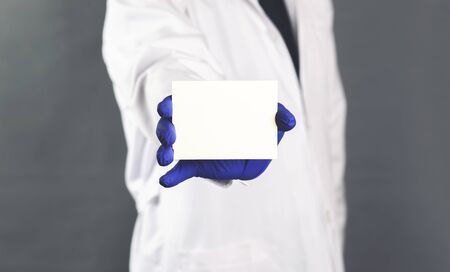 Male doctor hand holding and giving white blank calling card