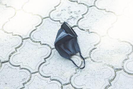 An used black face mask drop on the road, the face masks used for the anti-coronavirus that were used were left on the floor