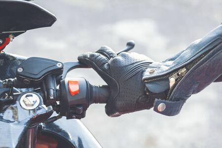 Closeup hand of man driving a motorbike on natural background Фото со стока