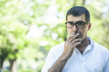 Young man in glasses smokes on the nature