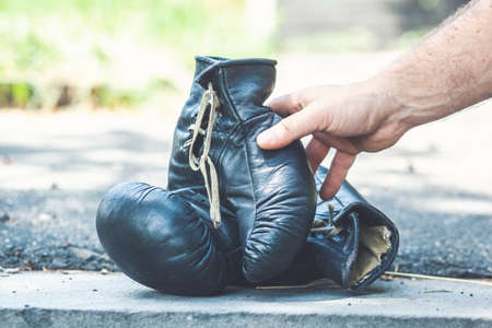 Young man hands holding a pair of boxing gloves on the nature