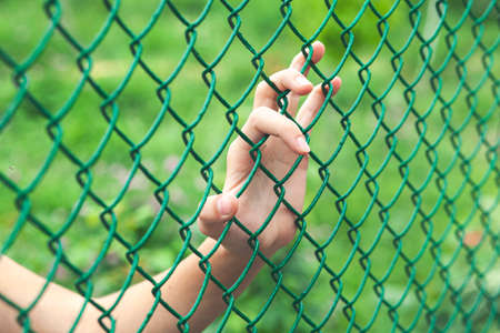 Female hand holding mesh fence, feeling no freedom and want to go to green world outside Stock fotó