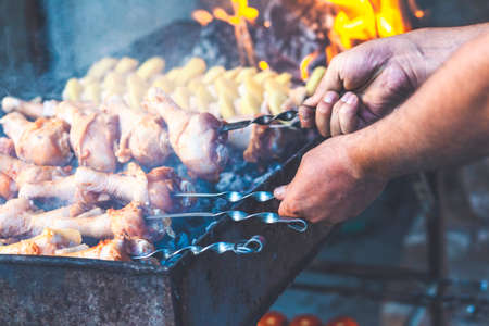 A man fries meat while cooking barbecue. Cooking meat in nature. Close-up