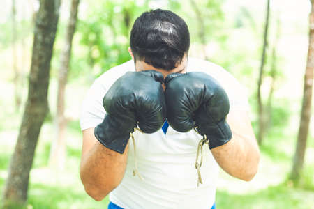 Boxing training endurance. Man athlete concentrated face with sport gloves practicing boxing nature background. Boxer ready to fight. Sportsman boxer training with boxing gloves. Stock fotó