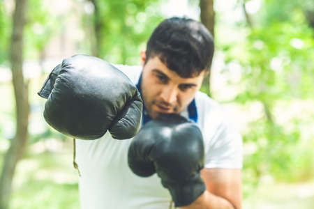 Boxing training endurance. Man athlete concentrated face with sport gloves practicing boxing nature background. Boxer ready to fight. Stock fotó