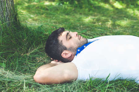 Handsome young man lying on the ground and relaxing in the park with his eyes closed Stock fotó