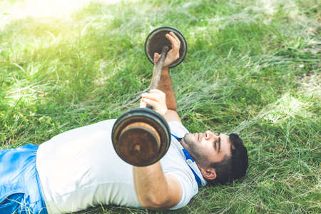 Sporty man in a white t-shirt and shorts pick up heavy barbell in nature