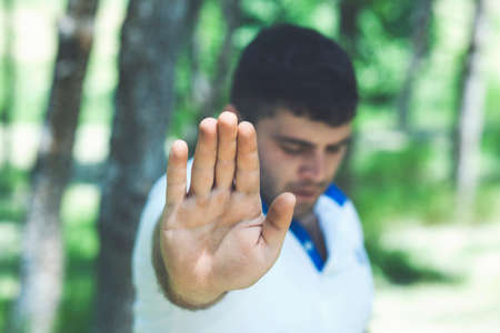 Young man with his hands shows stop in the nature