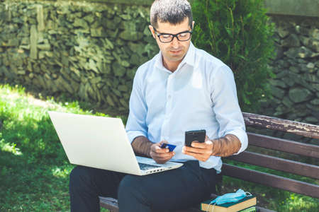 Young businessman working on laptop while sitting on bench