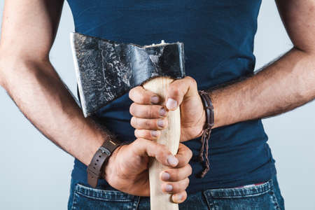 A man holds an ax in his hands against on gray background Stock fotó