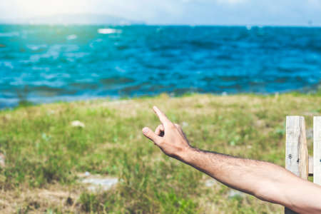 a young man points to a view of green fields on a cliff and the sea, as well as a blue sky with clouds