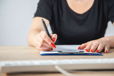 A woman writes with a pen in a notebook. 版權商用圖片