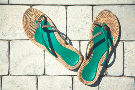 Colorful sandals on the terrace with tile floor in the summer sun 免版税图像
