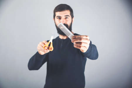 handsome man with long dark beard holding a hairbrush and scissors. hair and beard care in a hairdresser.