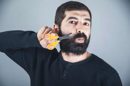 Bearded hairdresser, barber styllist cutting styling his own beard with scissors and comb 免版税图像