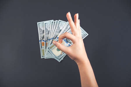 American dollars in the hands of a girl on a black background and the OK symbol are made by fingers.