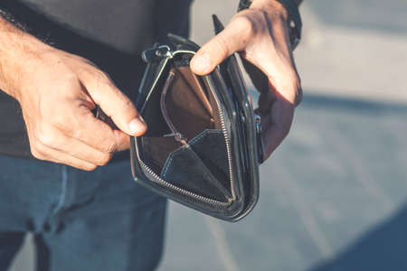 young man hand empty wallet on dark background