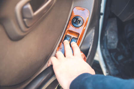 man is pulling lever of power window in automobile to lifting glass, closeup view of hand and finger, remote control
