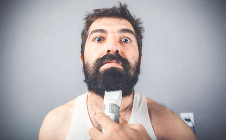 close up of young male person cutting his beard using the trimmer
