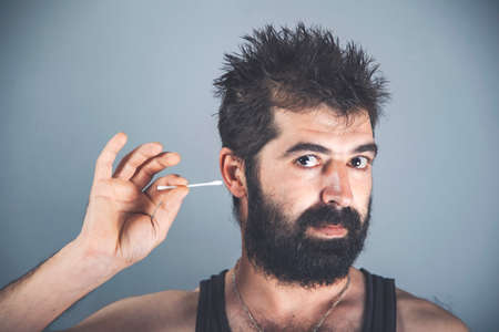 Man about to clean his ears using Q-tip cotton swab. Hygiene essentials concept. Removing wax from ear. 免版税图像
