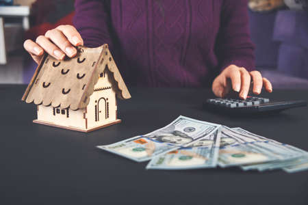 A woman holds in her hand a model of a house and money for real estate investment.