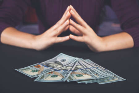 Woman holding and counting cash money american dollars in her hands on black table background. 免版税图像