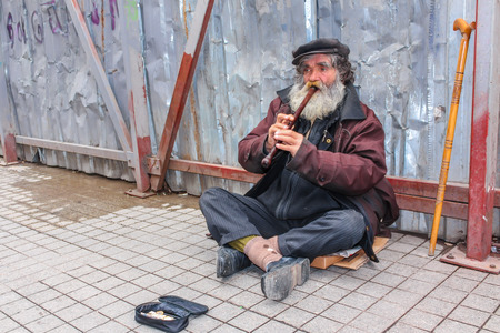 mendicant: ISTANBUL, TURKEY - MARCH 23: Busker playing flute on March 23, 2015 in Istanbul Editorial