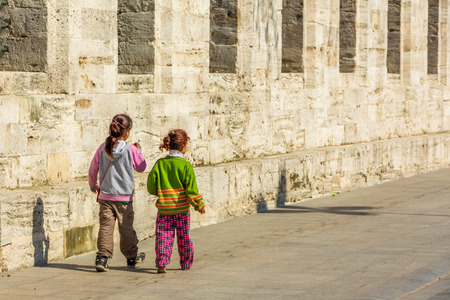 ni�os pobres: ESTAMBUL, Turqu�a - 11 de abril: Los ni�os pobres que caminan a lo largo de la pared el 11 de abril, 2015, en Estambul Editorial