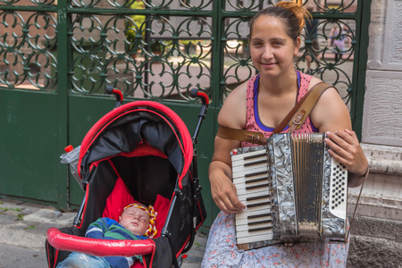 busker: ISTANBUL, TURKEY - MAY 24: The woman with the child to make money playing the accordion on May 24, 2015 in Istanbul