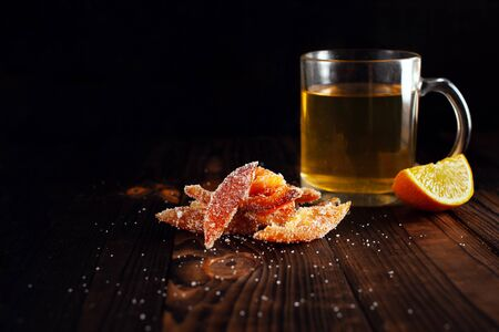 Orange peels in sugar. Candied fruit from aplsin. Orange marmalade on a wooden brown table with a black background. Tea with sliced orange. Empty space for text.