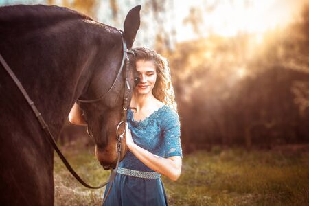 Beautiful girl in a blue dress hugs a horse. Fairytale photography, artistic, magical. Girl and horse in the sunset light. Love for horses. Banco de Imagens