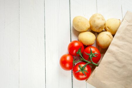 Beige paper bag on a wooden white background, vegetables from the store. Red tomatoes, yellow young potatoes. Empty space for text.