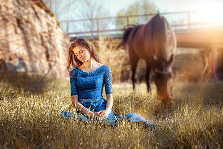 Beautiful girl in a blue dress is sitting on the grass. A brown horse grazes in the meadow. Fairytale photography, artistic. Girl and horse on a background of a bridge in the sunset.